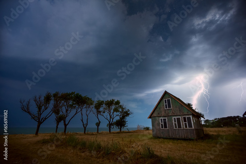 Zdjęcie XXL Stary drewniany dom nad brzegiem morza, noc burza na morzu
