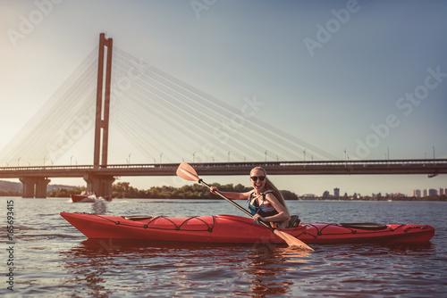 Valokuva  Woman kayaking on sunset