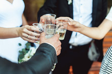 People Hold In Hands Plastic Cups With White Wine. Wedding Party.