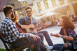 canvas print picture - Group of people hangout at the city street.They sitting on bench ,singing and playing guitar.