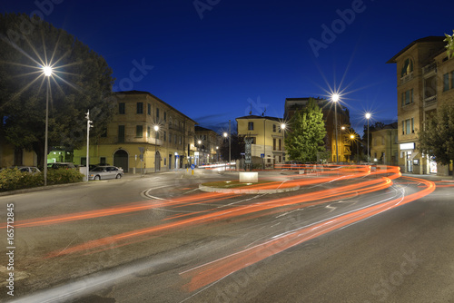 Car light trails on the crossroad during night in the city of Umbertide, Italy