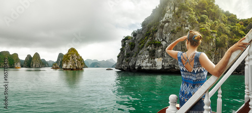 Pretty woman in a dress is traveling by boat in Halong Bay. Vietnam.