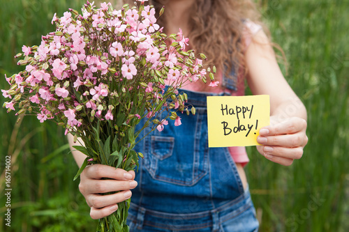 Photo  Beautiful woman with Happy birthday card and bouquet of pink flowers