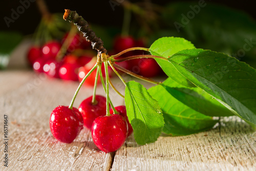 Branch of red cherries closeup on a wooden table Wallpaper Mural