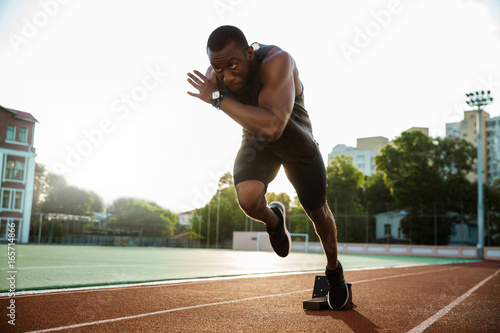 Photo Young african runner running on racetrack