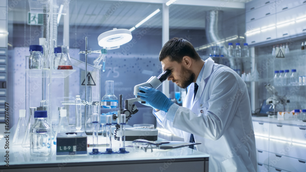 Fototapety, obrazy: Research Scientist Looks into Microscope. He's Conducts Experiments in Modern Laboratory.