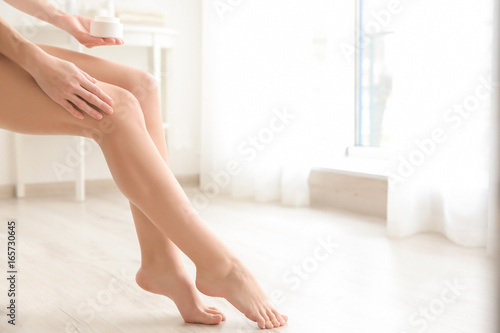 Obraz na plátně  Woman holding jar with cream near legs on light background