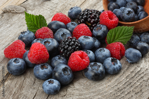 mix of blueberries, blackberries, raspberries in wooden bowl on old wooden table Wallpaper Mural