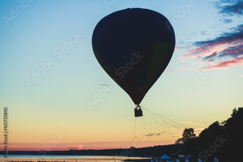 A flying aerostat hot air balloon in flight, with a sun dusk over the beach and Wallpaper Mural