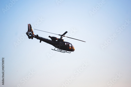 Tuinposter Helicopter A flying black helicopter aircraft during the flight with blue sky in the background