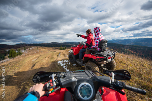 View from a quad bike. Couple sitting on atv. Man showing something for woman on the top of mountain under sky with clouds in the autumn mountains