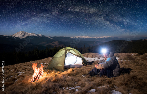 Obraz Male tourist have a rest in his camp at night. Man with lighting headlamp sitting near campfire and tent, looking to the camera under beautiful sky full of stars and milky way - fototapety do salonu