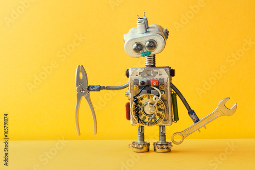 Hand wrench pliers robot handyman on yellow background. Cyborg toy lamp bulb eyes head, electric wires, capacitors vintage resistors.