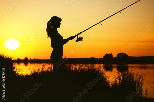 Silhouette of a woman engaged in sport fishing