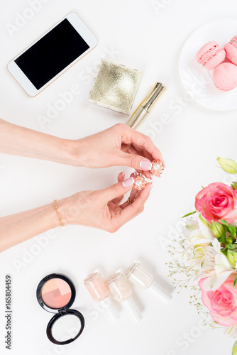 Aluminium Prints Manicure cropped shot of woman holding golden earrings above cosmetics, smartphone and flowers on white