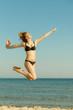 Woman wearing bikini playing, jumping near sea