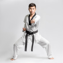 Portrait Of An Asian Professional Taekwondo Black Belt Degree (Dan) Preparing For Fight. Isolated Full Length On Grey Background With Copy Space