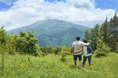 Photo  Middle-aged couple of tourists standing embraced and enjoying beautiful mountain