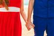 Close up of loving couple holding hands on a beach near the sea