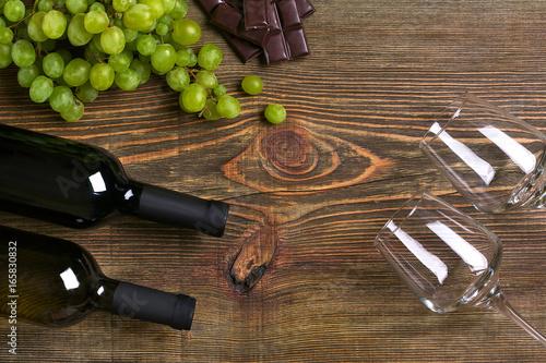 butelki-i-kieliszki-wina-czekolada-i-dojrzale-winogrona-na-drewnianym-tle