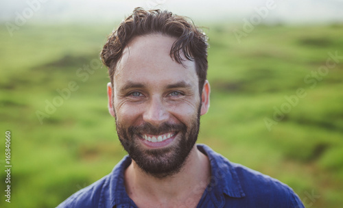 Bearded man with brown hair looking happy outside in nature