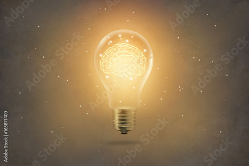 Fotomural golden brain glowing inside light bulb on paper texture background