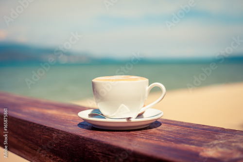 Poster Cafe A cup of coffee in a white cup on beach background