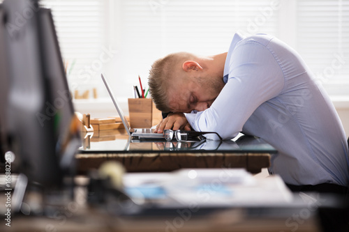 Businessman Sleeping Over The Desk Poster