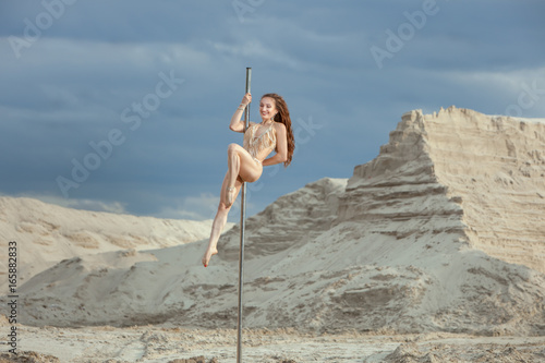 Fotografía  Woman performs tricks on the pole she is dancing pole dance.