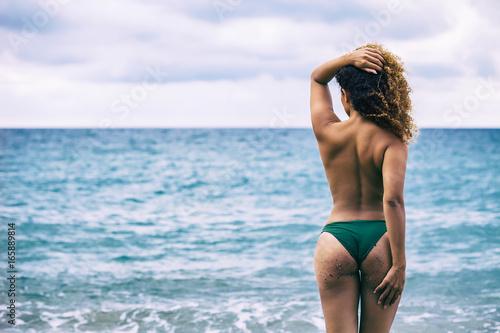 Zdjęcie XXL Tylny portret piękna kobieta patrzeje morze z wspaniałym kędzierzawym włosy