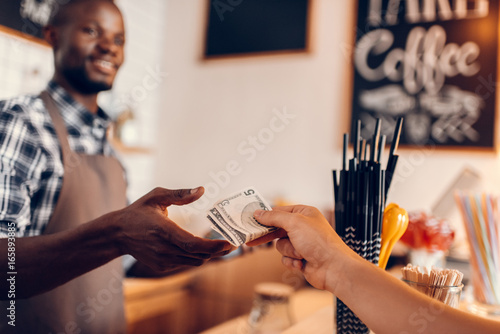 Cuadros en Lienzo handsome smiling african american barista taking cash payment on bar counter in