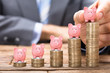 Businessman Placing Piggybank On Stacked Coins