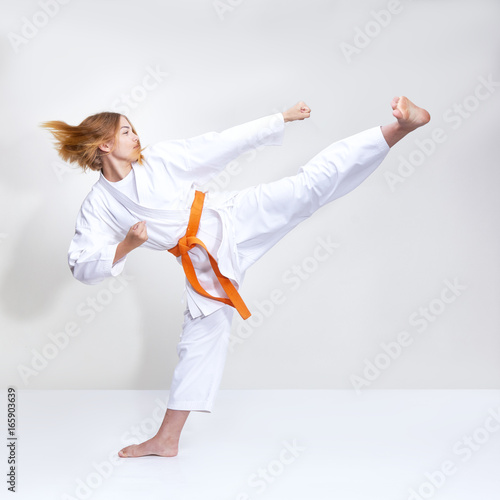 Photo Stands Martial arts Kicking a foot in the performance of an athlete in karategi