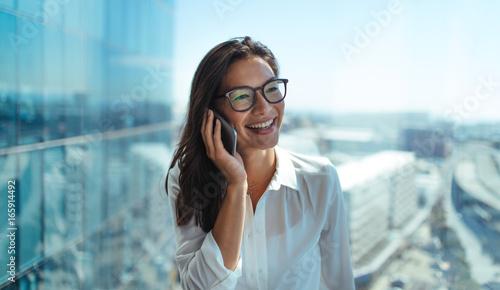 Fotografía  Smiling woman entrepreneur talking over phone.