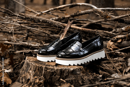 57e590b3c8c Black shiny patent leather women s loafers with white soles on old wood in  a forest or park.