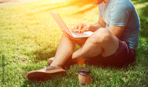 Leinwand Poster Young blogger sitting on grass and working with laptop