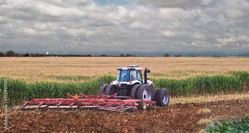 Obraz na plátne A farmer uses a disc harrow to roll corn stubble back into the soil for nutrients for next season