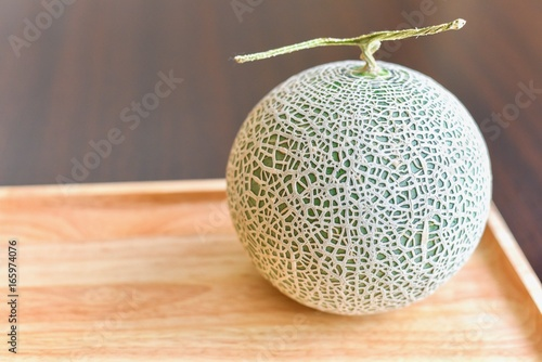 Close-Up View of Green Cantaloupe Melon Isolated on Wooden Board