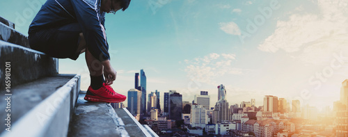 Asian Guy Tying Running Shoe, Preparing for Running, with Panoramic City background in Sunrise - 165981201