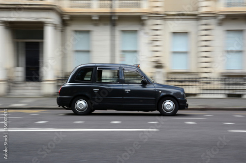 Valokuva  Panning shot of a black taxi in London.