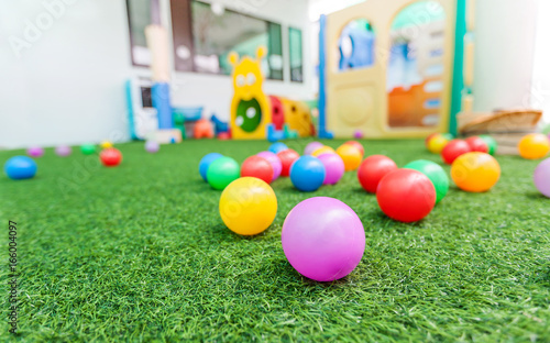 colorful plastic ball on green turf at school playground Canvas Print