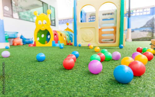 colorful plastic ball on green turf at school playground Wallpaper Mural
