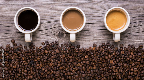 Keuken foto achterwand Koffiebonen varietà di caffè in tazzina su sfondo legno