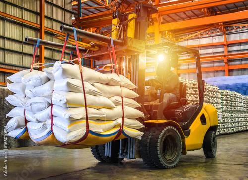 Fotografie, Obraz  Forklift handling sugar bag for stuffing into container for export,