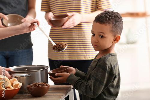 Photo Cute little boy waiting for food. Poverty concept