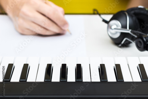 Obraz na plátne  songwriter hands writing song with piano and headphone on desk, focus on piano k