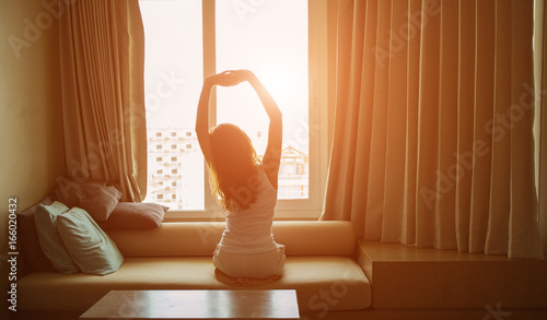 Photo  A low key of  woman waking up and stretching in the eary morning.