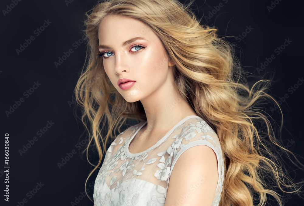 Fototapeta Blonde fashion  girl with long  and   shiny curly hair .  Beautiful  model  in light blue dress with wavy hairstyle .