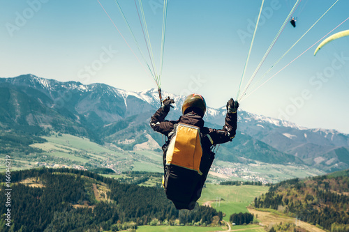 Fotobehang Luchtsport Paraglider is on the paraplane strops - soaring flight moment