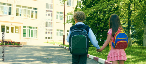 back view of two pupils of primary school go hand in hand boy and